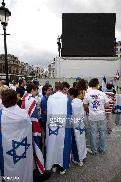 Crowds look on after a proPalestine demonstrator scales the mobile television screen to demonstrate during the Salute to Israel Parade in Trafalgar...