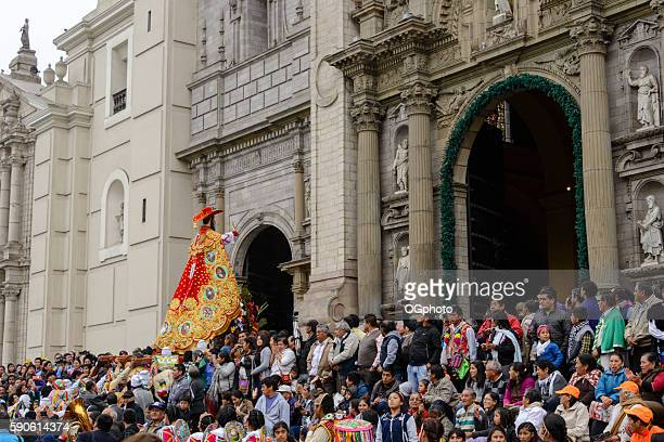 Crowds observing religious procession in front of cathedral