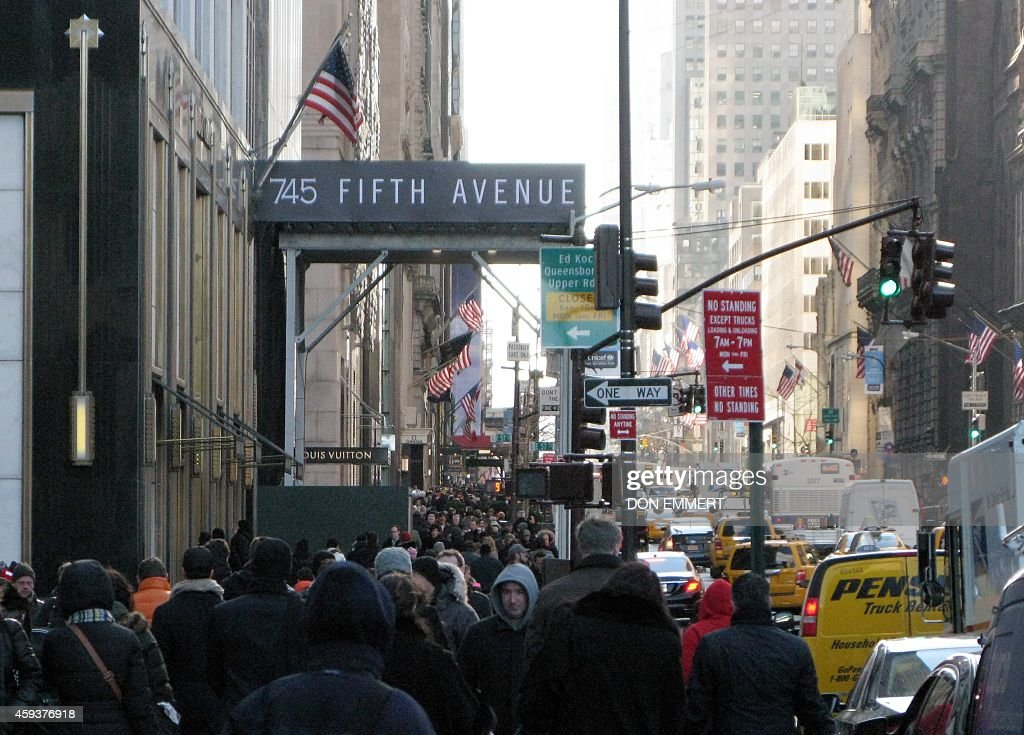 Crowds of bundled up pedestrians walk along 5th Avenue November 21 2014 in New York Cold temperatures and high winds made for a cold day of shopping...