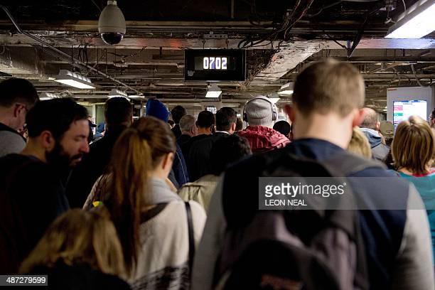 Crowds of commuters gather before the gates are opened at Victoria station in London on April 29 as a planned 48 hour underground train strike came...