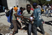 Crowds of locals looted the devestated Carribean Market on Friday morning while scores of dead remain trapped inside Haiti's largest supermarket...