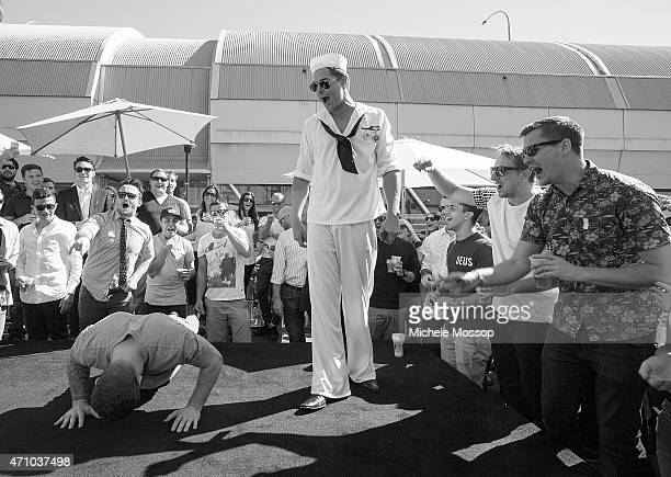 Crowds of people at the Australian Hotel play Twoup in the Rocks on April 25 2015 in Sydney Australia The 'Spinner' is made to do push ups when the...