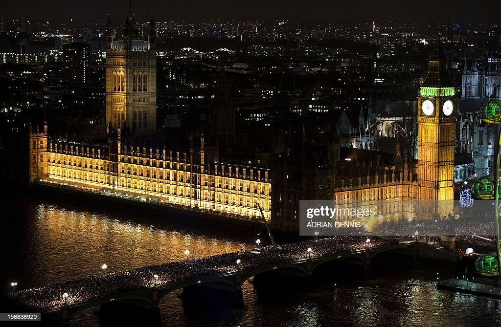 Crowds of people gather on Westminster Bridge to watch the New Year fireworks close to The House of Parliament in central London just before midnight in London on December 31, 2012.