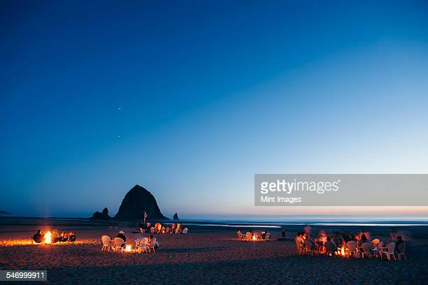 Crowds of people sitting by glowing campfires on Cannon Beach at dusk. Haystack Rock in the background.
