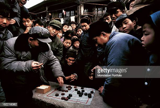 Crowds of people surround two players of Chinese draughts in the alley of a suburb of Peking Peking January 1973