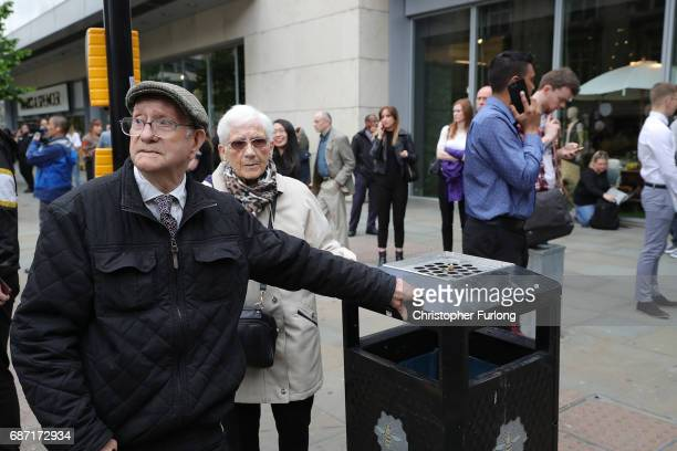 Crowds of people wait outside after police avacuated the Arndale Centre on May 23 2017 in Manchester England An explosion occurred at Manchester...