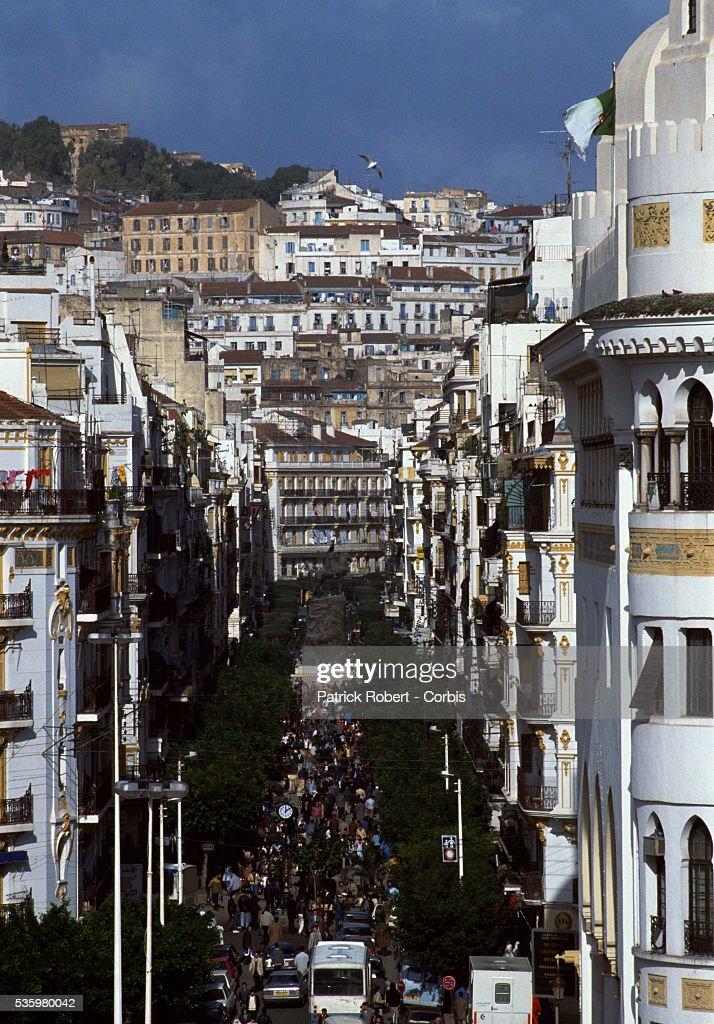 Crowds of people walk through a street in Algiers.