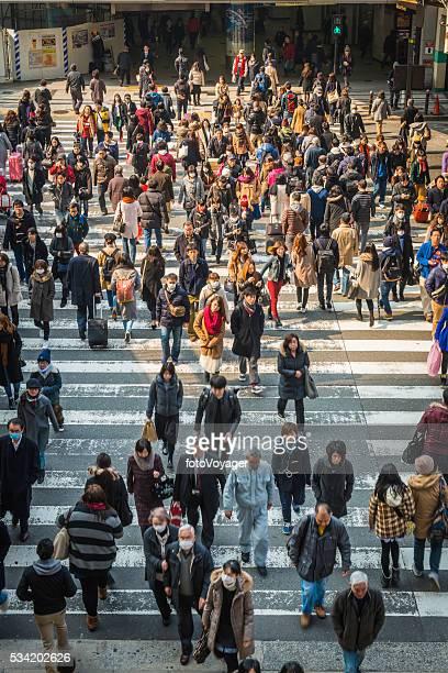 群衆のラッシュアワーの通勤者の歩行者横断オサカ日本
