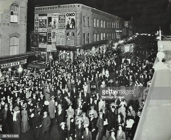 Crowds of shoppers in Rye Lane at night Peckham London 1913 Shoppers throng the street at 10 o'clock at night On the right is a doubledecker bus with...