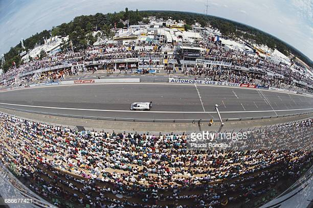 Crowds of spectators look on as the Team Sauber Mercedes C9 MercedesBenz V8 driven by Jochen Mass Manuel Reuter and Stanley Dickens powers down the...