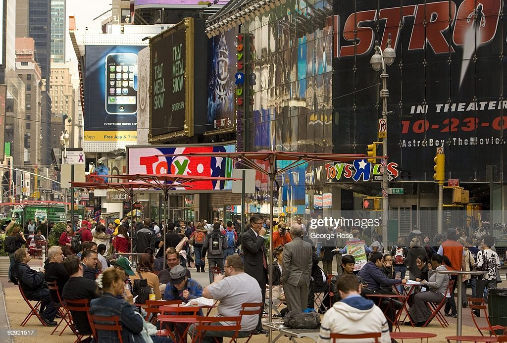 Crowds of tourists gather in the new Times Squre pedestrian median as seen in this 2009 New York, NY, early evening cityscape photo.