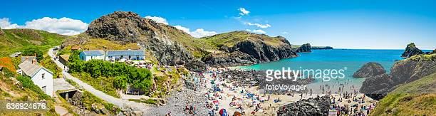 Crowds of tourists on summer holiday beach Kynance Cove Cornwall