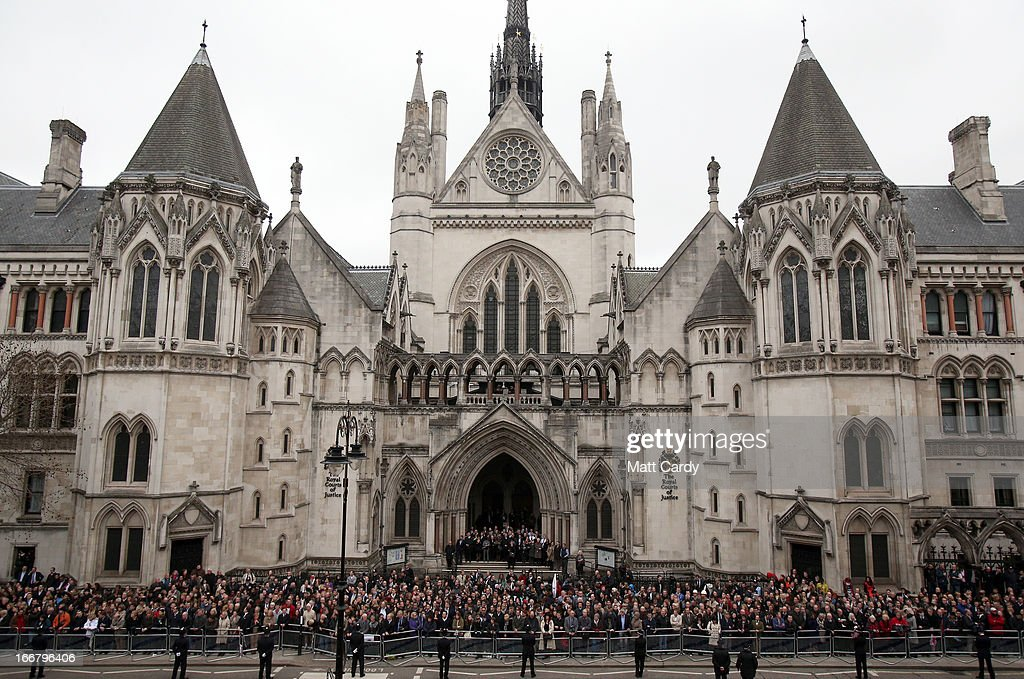 Crowds on the steps of the Royal Courts of Justice gather to watch as a Gun Carriage of The King's Troop Royal Horse Artillery carries the coffin of...