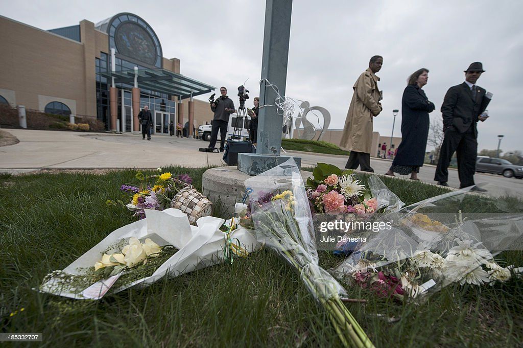 Crowds pass by a makeshift memorial following an interfaith service honoring victims of Sunday's shootings on April 17, 2014 at the Jewish Community Center of Greater Kansas City, in Overland Park, Kansas. White supremacist Frazier Glenn Cross is in custody, charged with murder in the killing of two people outside the center and a third victim at a nearby Jewish retirement home on April 13.