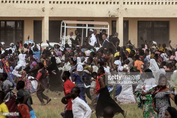 Crowds run after Pope Francis as he waves during a visit to the Koudoukou school to meet members of the muslim community after leaving the Central...