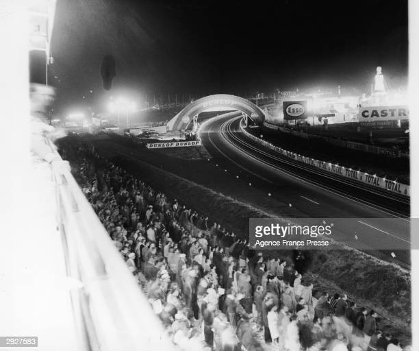Crowds stand and watch the 24 Hour Le Mans Race at night France June 24 1962