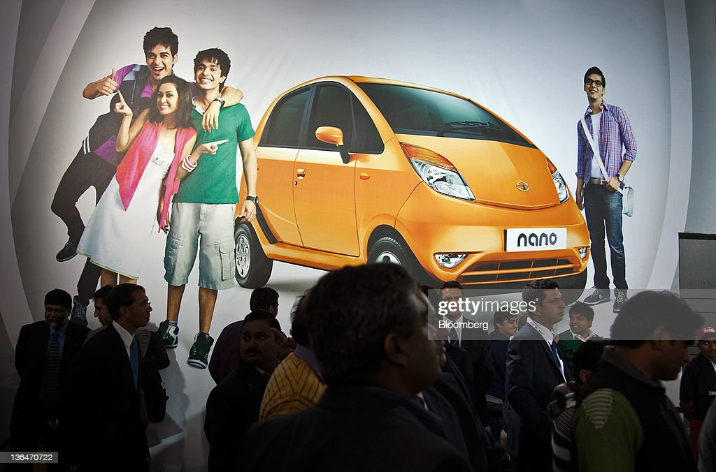 Crowds stand in front of an advertisement for Tata Motors Ltd's Nano hatchback vehicle at the Auto Expo 2012 in New Delhi India on Thursday Jan 5...