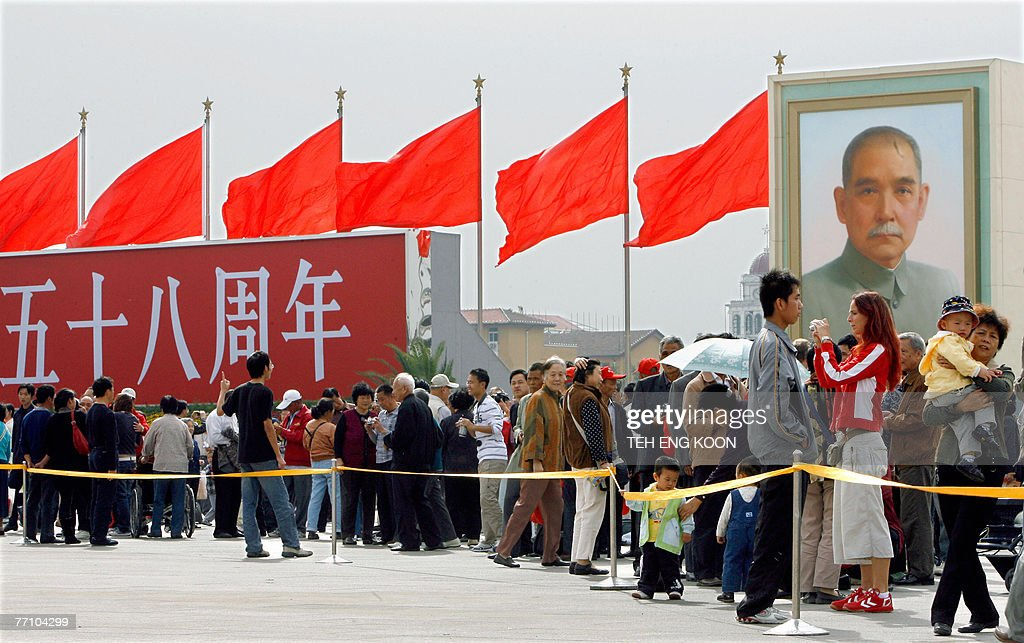 Crowds stand near a portrait of the founder of modern China Sun Yat-en displayed at the Tiananmen Square in Beijing, 29 September 2007. The Chinese capital is gearing up for its 58th National Day celebration 01 October and the 17th Communist Party Congress in mid-October, which could lead to personnel changes in the top echelons of power and will set China's political and economic course for the next five years. AFP PHOTO/TEH ENG KOON