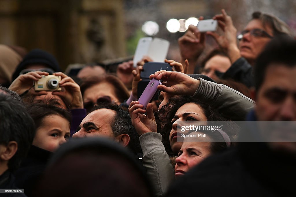 Crowds take photos while watching as Pope Francis appears in the window of his private residence in St Peter's Square to give his first Angelus blessing on March 17, 2013 in Vatican City, Vatican. The Vatican is preparing for the inauguration of Pope Francis on March 19, 2013 in St Peter's Square.