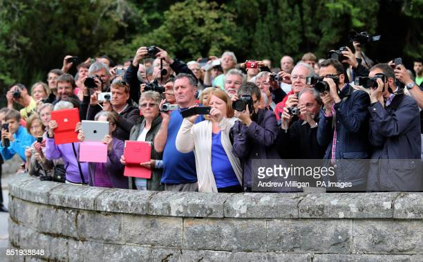 Crowds take pictures as Queen Elizabeth II inspects the Royal Scots Borderers at the gates to Balmoral as she takes up summer residence there