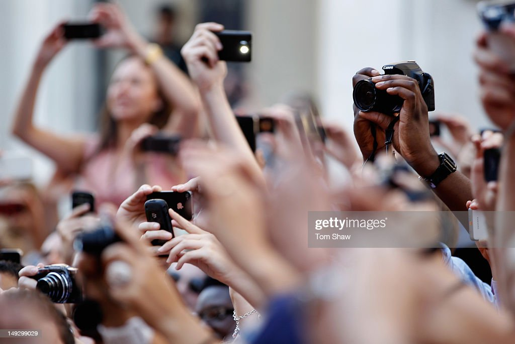 Crowds take pictures in their camera phones and smart phones as torch bearer carrries the Olympic Torch through Central London on July 26, 2012 in London, England.