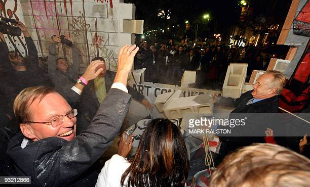 Crowds tear down a mockup of the Berlin Wall at an event commemorating the 20th anniversary of the fall of the Wall on Wilshire Blvd in Los Angeles...