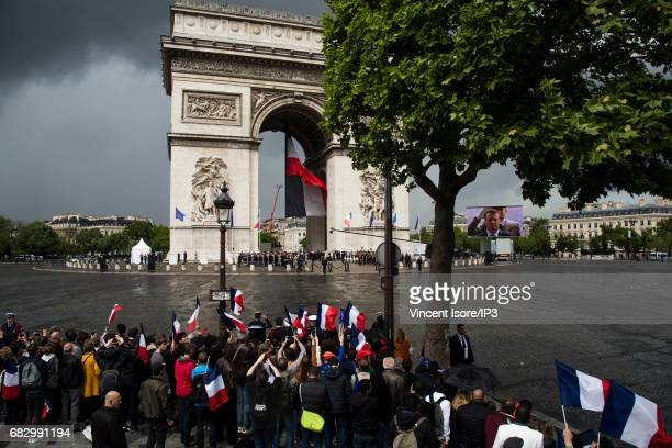 Crowds wait for New French President elected Emmanuel Macron to travel up the Champs Elysees avenue in order to attend a tribute ceremony of the...