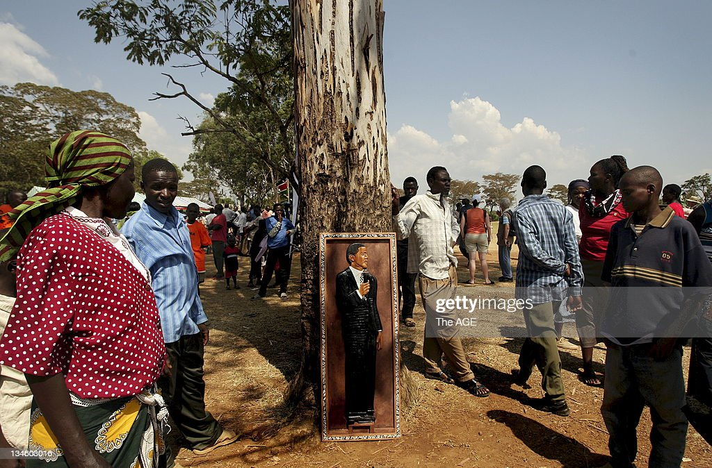 Crowds walk past a wooden relief of Barak Obama at the Senator Obama primary school in Kogelo, Kenya,. Thousands gathered before a small tv and another screen to watch the inauguration of Barack Obama live as he is sworn in as the 44th President of The United States of America. Kogelo is the Kenyan village where his father Barak Obama Senior was born and the Presidents grandmother lives. Kogelo, Kenya. Today 20th January, 2009.