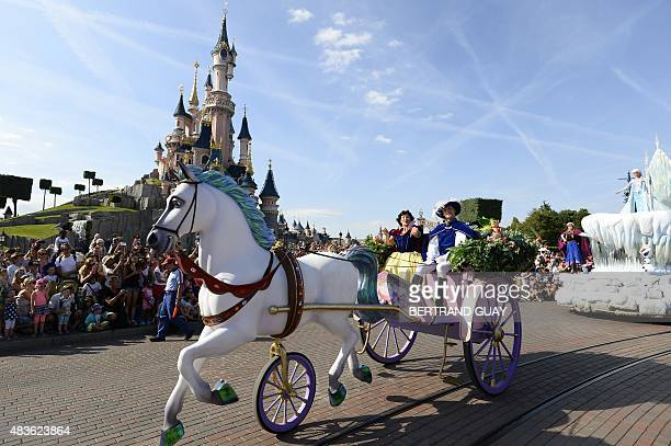 Crowds watch as Snow White and her prince ride past on a carriage during the Main Street Parade at Disneyland Paris in MarnelaVallee on August 6 2015...