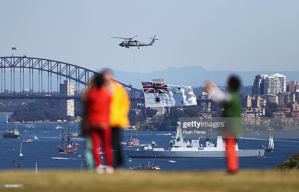 Crowds watch on from Dover Heights as Division 3 boats enter the Harbour during the International Fleet Review on October 4, 2013 in Sydney, Australia. Over 50 ships will participate in the International Fleet Review at Sydney Harbour to commemorate the 100 year anniversary of the Royal Australian Navy's fleet arriving into Sydney. Prince Harry will take part in the fleet review during his two-day visit to Australia.