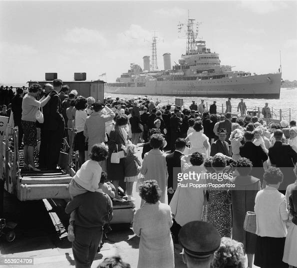 Crowds watch the arrival of the Royal Navy light cruiser HMS Belfast as she arrives in Portsmouth after naval exercises in the Far East 19th June...