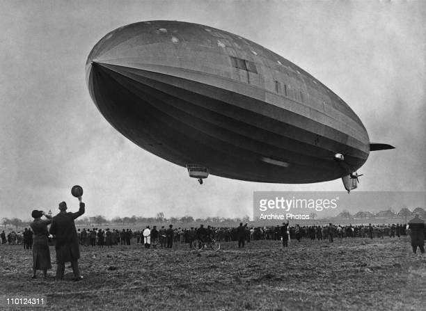 Crowds watch the German LZ 129 Hindenburg airship making its first test flight from the Zeppelin dockyards at Friedrichshafen Germany 4th March 1936...
