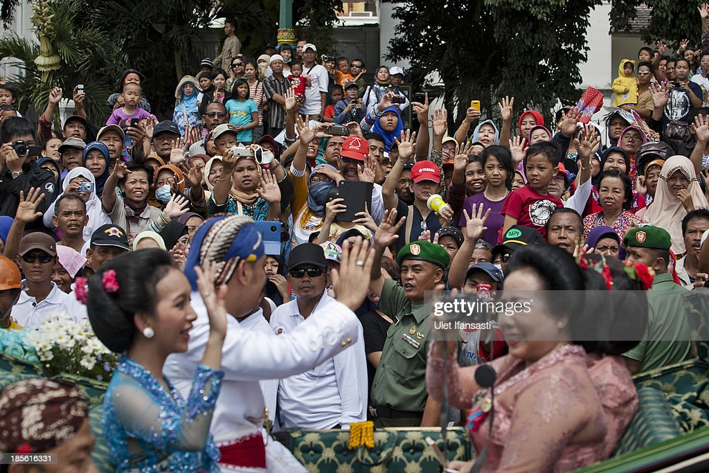 Crowds wave to Kraton Palace family while on their journey by carriage during the wedding ceremony parade as part of the Royal Wedding Held For Sultan Hamengkubuwono X's Daughter Gusti Ratu Kanjeng Hayu And KPH Notonegoro on October 23, 2013 in Yogyakarta, Indonesia. Wedding celebrations will take place between October 21st and 23rd. The wedding parade will include 12 royal horse drawn carriages and will be streamed live on the internet so that it can be watched by people all over the world.