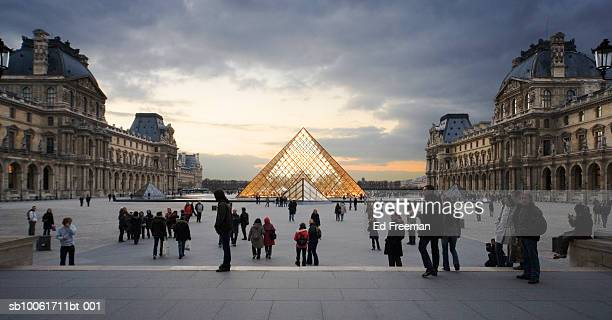 Crowed outside Louvre museum at sunset