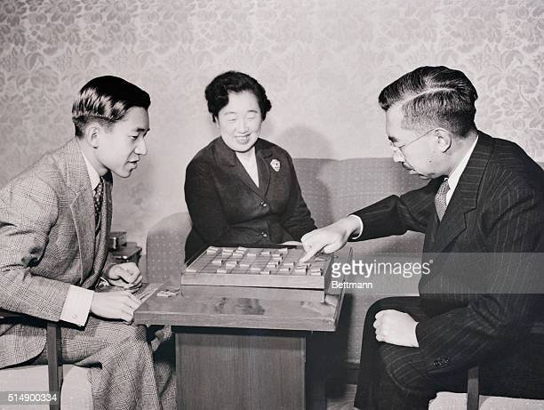 Crown Prince Akihito of Japan who had just turned 21 gets better acquainted with his father Emperor Hirohito over a game of Shogi or Japanese Chess...