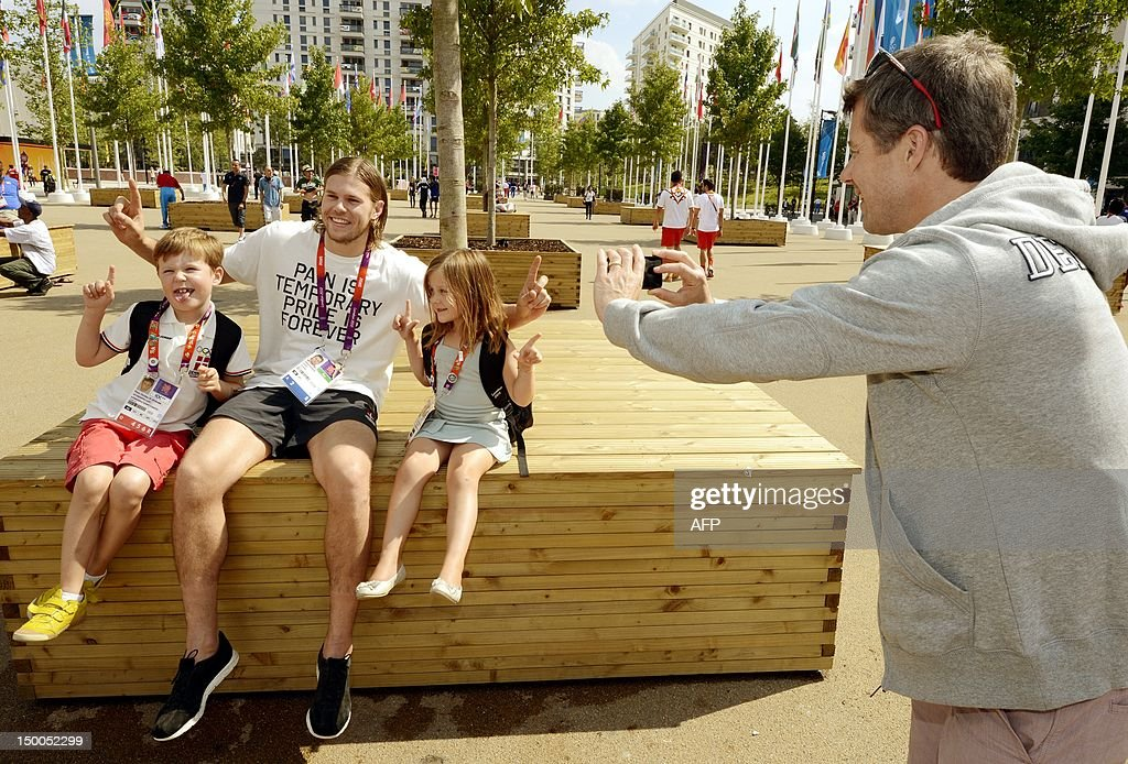 Crown Prince Frederick of Denmark (R) takes a picture of his children Prince Christian (L) and Princess Isabella (2nd R) as they sit with Danish athletes Mikkel Hansen during a visit to the London 2012 Olympic Games athlete's village in London on August 9, 2012. AFP PHOTO / John Stillwell / POOL