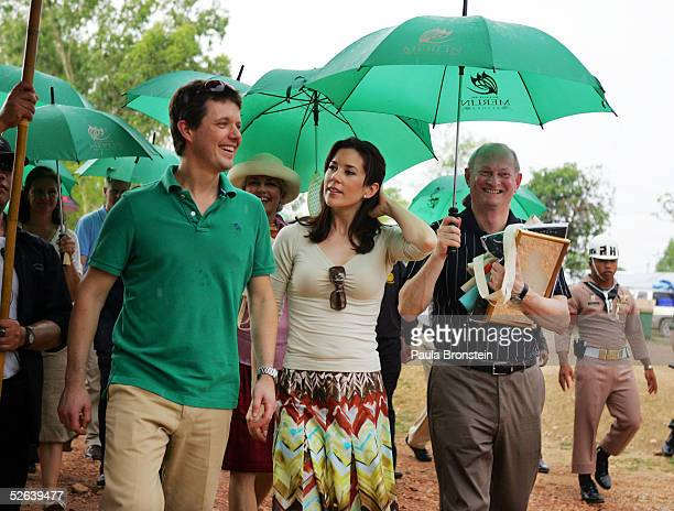 Crown Prince Frederik and the Crown Princess Mary of Denmark chat during a walking tour on their visit to a shelter for hundreds of villagers left...