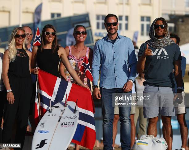 Crown Prince Haakan Of Norway watches the evening competition alongside Norway Surf Team members Guro Aanestad Ase Odegaard and Joackim Guichard...