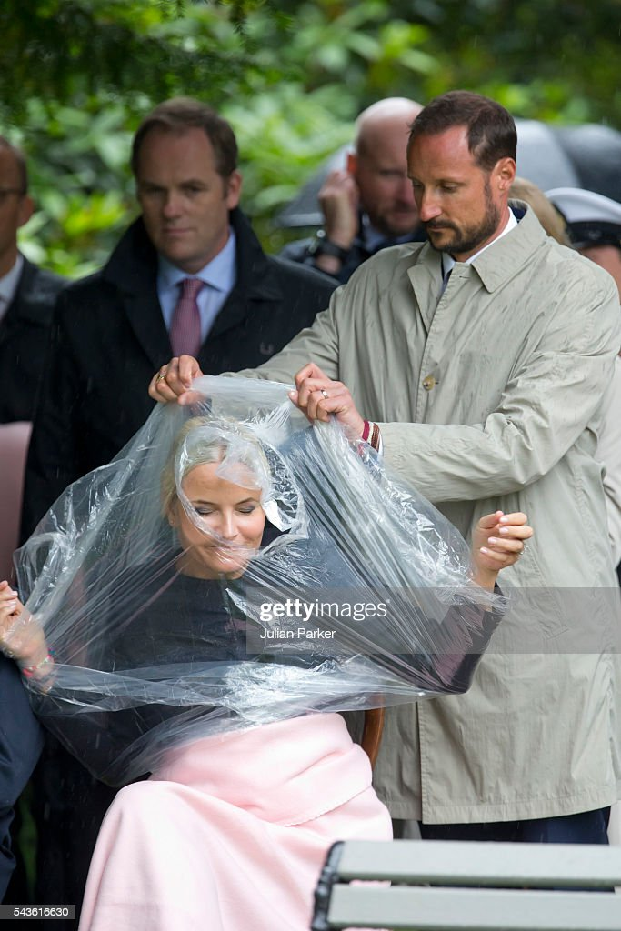 <a gi-track='captionPersonalityLinkClicked' href=/galleries/search?phrase=Crown+Prince+Haakon+of+Norway&family=editorial&specificpeople=158362 ng-click='$event.stopPropagation()'>Crown Prince Haakon of Norway</a> ( right ) , assists his wife, Crown Princess Mette-Marit of Norway, putting on a rain poncho, on a visit to Kristiansand, during the King and Queen of Norway's Silver Jubilee Tour, on June 29, 2016 in Kristiansand, Norway.
