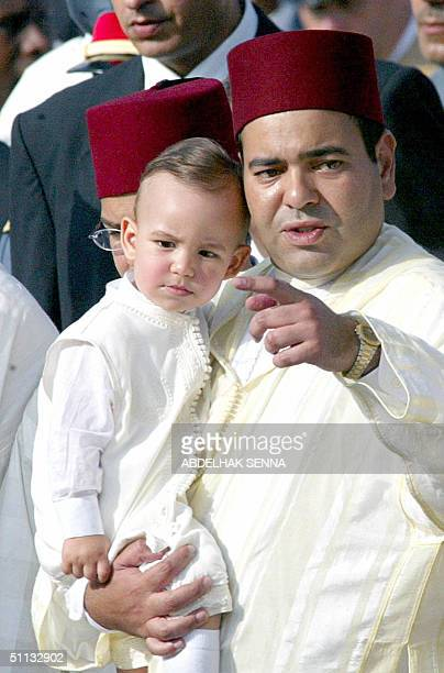 Crown Prince Moulay Hassan in the arms of his uncle Prince Moulay Rachid participates in a procession at the royal palace of Rabat 31 July 2004 where...