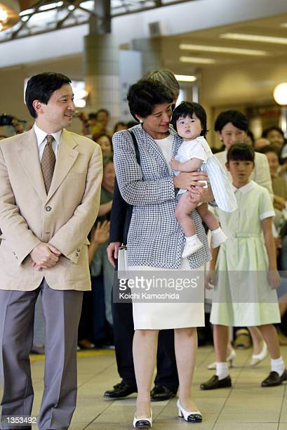 Crown Prince Naruhito and Crown Princess Masako holds her daughter Princess Aiko in front of Izukyushimoda station August 25 2002 in Shizuoka Japan...