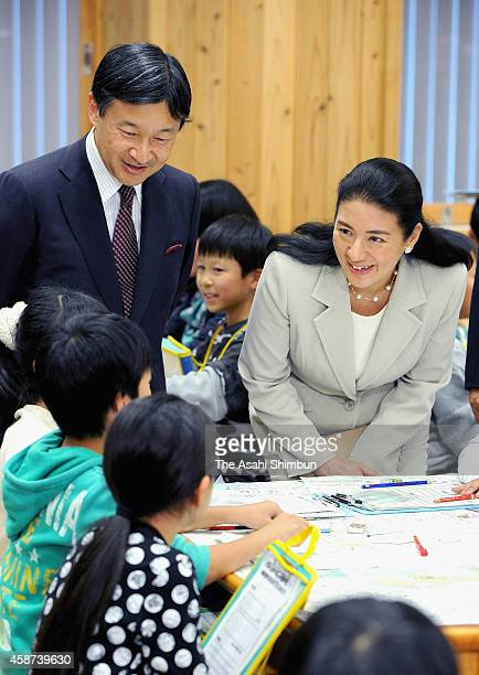 Crown Prince Naruhito and Crown Princess Masako speak to children at an education facility for irrigation on November 10 2014 in Anjo Aichi Japan