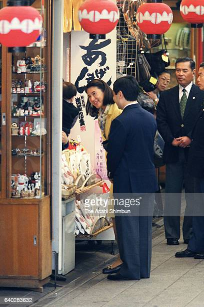 Crown Prince Naruhito and Crown Princess Masako talk to local residents while strolling the Nakamise street of Asakusa on April 22 1999 in Tokyo Japan