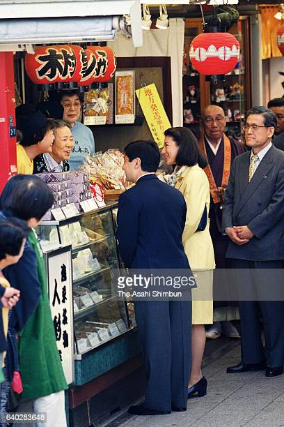 Crown Prince Naruhito and Crown Princess Masako talk to staffs at a shop while strolling the Nakamise street of Asakusa on April 22 1999 in Tokyo...