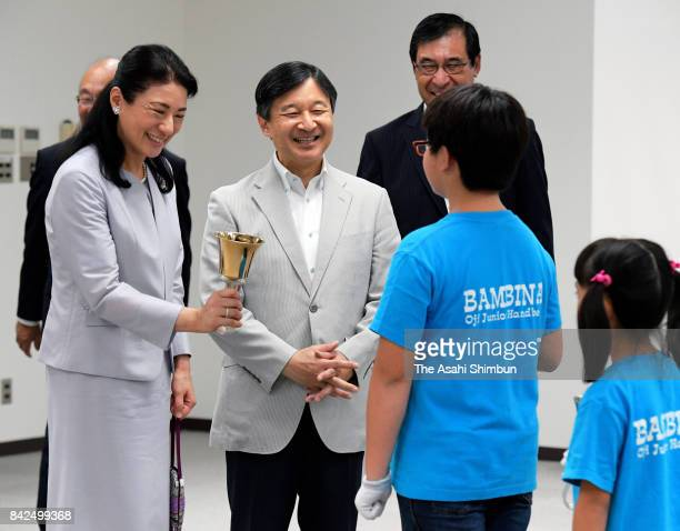 Crown Prince Naruhito and Crown Princess Masako talk with participants after watching hand bell performance at Oji City Culture Walfare Center on...