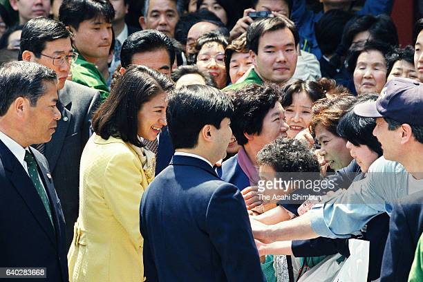 Crown Prince Naruhito and Crown Princess Masako talk with wellwishers while strolling the Nakamise street of Asakusa on April 22 1999 in Tokyo Japan