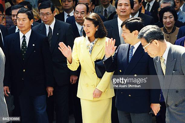 Crown Prince Naruhito and Crown Princess Masako wave to wellwishers while strolling the Nakamise street of Asakusa on April 22 1999 in Tokyo Japan