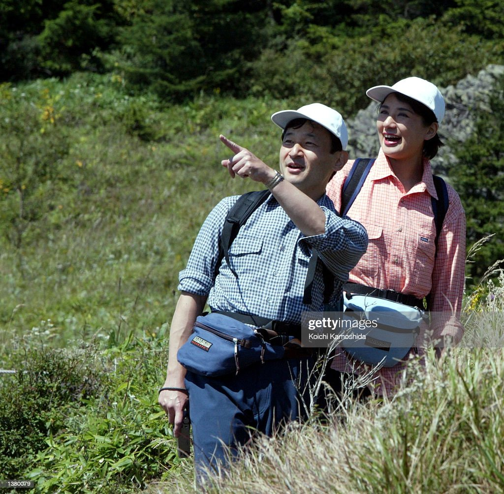 Crown Prince Naruhito gestures as Crown Princess Masako stands next to him while on a mountain peak named Kanbeiiwa September 12, 2002 in Enzan, Yamanashi Prefecture, Japan. The royal couple are climbing a mountain near Daibosatsu Touge.