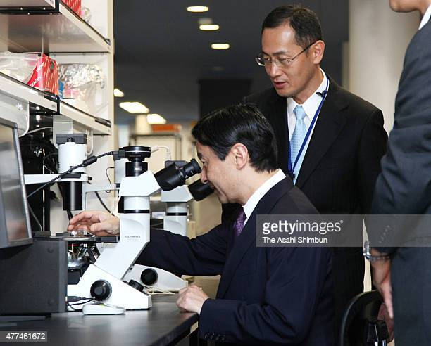 Crown Prince Naruhito looks into a microscope while Kyoto University Professor Shinya Yamanaka explains duirng his visit to the Center for iPS Cell...