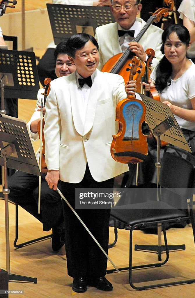 Crown Prince Naruhito shows the viola made of debris of the tsunami of the magnitude 9.0 earthquake in 2011, during the Gakushuin University Alumni Orchestra regular concert at Tokyo Metropolitan Theatre on July 7, 2013 in Tokyo, Japan.